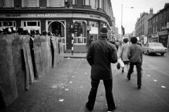 Police cordon off Railton Road by The Atlantic which was later destroyed buy rioters. Members of the public continue to shop in Coldharbour lane, despite the destruction only streets away.