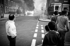 Residents from nearby houses look on as a car burns.