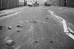 Rioters gather toward the end of a deserted and rock-strewn Railton Rd. To the right, an abandonded police van.